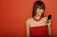 Young woman in red tube top using mobile phone - Yukmin