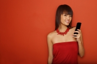 Young woman in red tube top with mobile phone - Yukmin