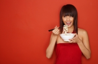 Young woman standing against red wall, eating a bowl of noodles - Yukmin