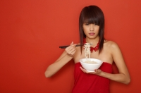 Young woman holding bowl of noodles, looking at camera - Yukmin