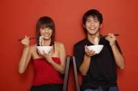 Couple sitting against red wall, holding bowl of noodles, smiling at camera - Yukmin