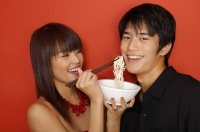 Young woman feeding man with noodles - Yukmin