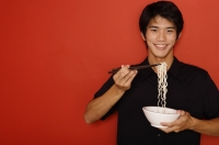 Man standing against red wall, holding bowl of noodles - Yukmin
