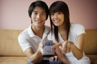 Couple on sofa, holding TV remote control - Yukmin