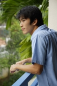 Young man leaning on railing, looking away - Yukmin