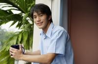 Young man holding mug, smiling at camera - Yukmin