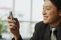 Businessman looking at mobile phone - Alex Mares-Manton
