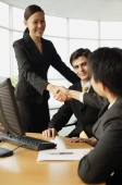 Businesswoman shaking hands on seated businessman in office - Alex Mares-Manton