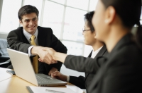 Business people shaking hands across table - Alex Mares-Manton