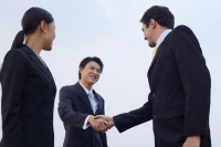 Businesspeople shaking hands, low angle view - Alex Mares-Manton