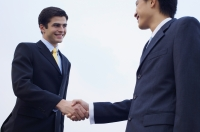 Businessmen shaking hands, low angle view - Alex Mares-Manton