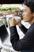 Man sitting in front of laptop, holding cup, looking away - Alex Mares-Manton