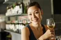 Woman at bar, holding wine glass, smiling at camera - Alex Mares-Manton