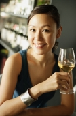 Woman at bar, holding wine glass, smiling at camera, portrait - Alex Mares-Manton