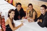Couples sitting in restaurant, having wine, smiling at camera - Alex Mares-Manton