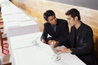 Two men sitting at table in restaurant, using laptop - Alex Mares-Manton