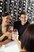 Young adults in restaurant, holding wine glasses, toasting - Alex Mares-Manton