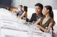 Couples dining in restaurant, man smiling at camera - Alex Mares-Manton