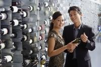 Couple in wine cellar, looking at camera - Alex Mares-Manton