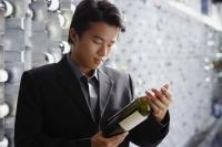 Man in wine cellar, looking at bottle of wine - Alex Mares-Manton