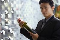 Man in wine cellar, holding bottle of wine - Alex Mares-Manton