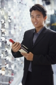 Man in wine cellar, holding bottle of wine, smiling at camera - Alex Mares-Manton