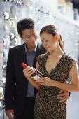 Couple in wine cellar, woman looking at wine bottle - Alex Mares-Manton