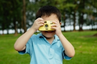 Young boy taking pictures with yellow camera - Yukmin