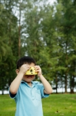 Young boy in park using camera - Yukmin