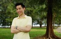 Man standing in park, smiling at camera, arms crossed - Yukmin