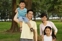 Family of four, standing in park, smiling at camera - Yukmin