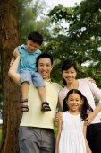 Family of four, standing outdoors, family portrait - Yukmin
