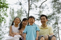 Family of four outdoors, smiling at camera - Yukmin