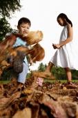 Children kicking leaves in park - Yukmin