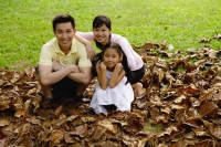 Family with one child crouching on pile of leaves, looking at camera - Yukmin