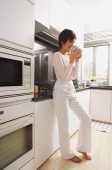 Young woman standing in kitchen, drinking coffee - Alex Mares-Manton