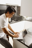 Man sitting at kitchen counter, using laptop - Alex Mares-Manton