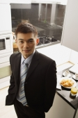 Businessman in kitchen, looking up at camera - Alex Mares-Manton