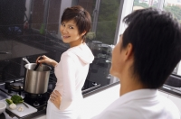 Woman cooking on stove, looking over shoulder at man standing behind her - Alex Mares-Manton