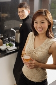 Couple in kitchen, man cooking at stove, woman holding wine glass - Alex Mares-Manton