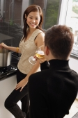Couple in kitchen, woman cooking at stove, man drinking wine glass - Alex Mares-Manton