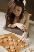 Woman lying on floor, playing with Chinese chess board - Alex Mares-Manton
