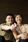 Couple watching TV, man holding remote control - Alex Mares-Manton