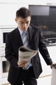 Businessman in kitchen, looking at newspaper - Alex Mares-Manton
