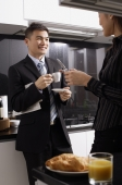 Executives in kitchen, man having coffee, woman holding mobile phone - Alex Mares-Manton