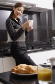 Female executive standing in kitchen, holding mug - Alex Mares-Manton