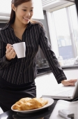 Female executive standing in kitchen, holding mug, looking at laptop - Alex Mares-Manton