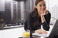 Female executive in kitchen with laptop, hand on chin, smiling at camera - Alex Mares-Manton