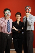 Businesswoman standing between two businessmen with Chinese masks over their faces - Marcus Mok