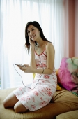 Woman on bed, listening to MP3 player - Yukmin